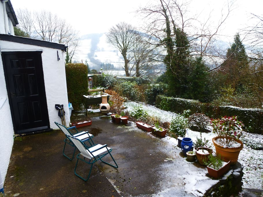 The terrace of the cottage facing the Dyfi Valley after recent snowfall. Good for coffee, birds, meals and the muse!