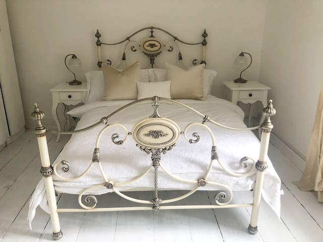 Double bed with white cotton bedding.