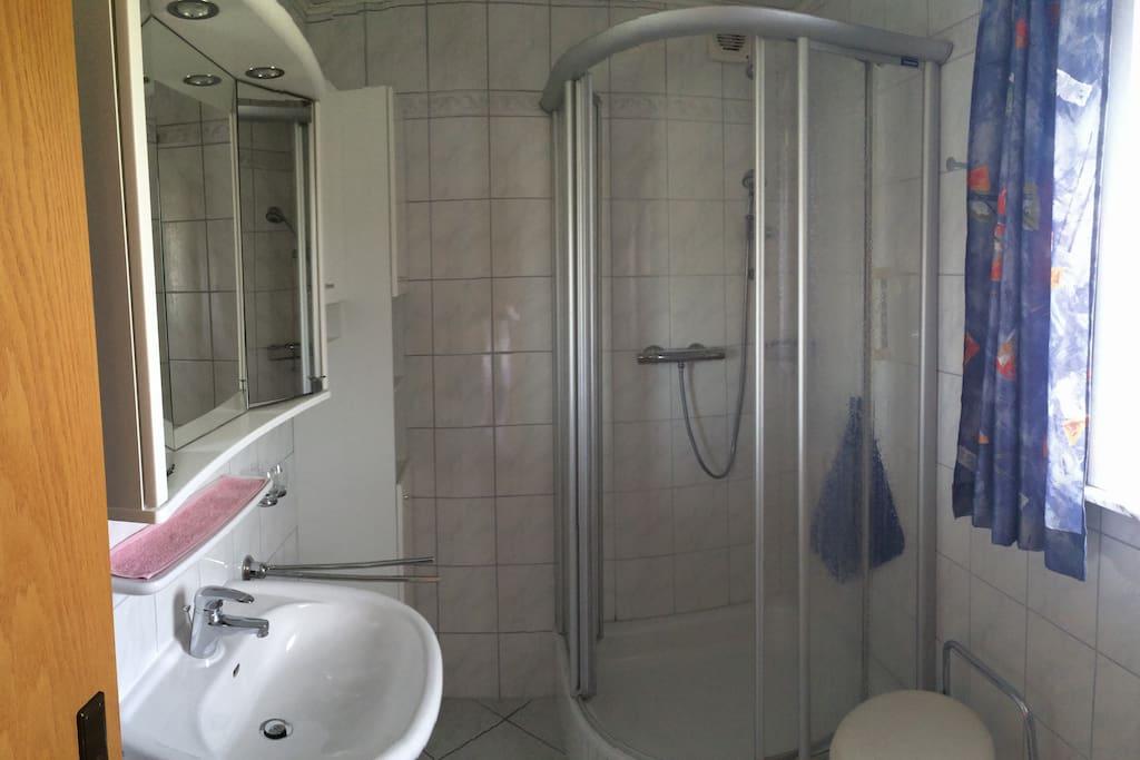 Sicht auf die Dusche und Waschbecken im Bad