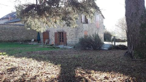 Maison en pierre dans cadre verdoyant.