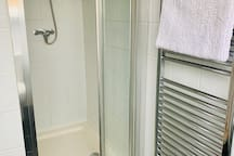 Shower with glass bi-folding door and heated towel rail.