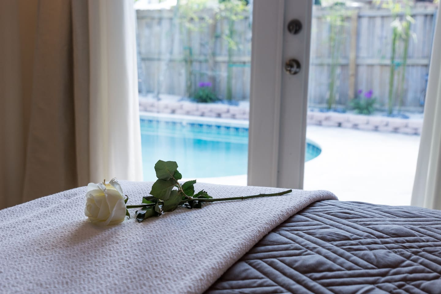 Queen sized bed with french doors to the pool