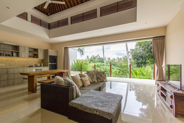 Sliding doors in the living room open seamlessly to the stone tiled balcony overlooking the jungle.