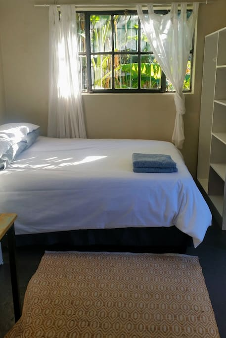 A comfortable Queen sized bed with clean linen and towels and a good sized cupboard. The North facing window overlooks the private back garden and gets dappled morning sunlight. More storage space is available for bags and suitcases in the laundry room, which is in the back garden.