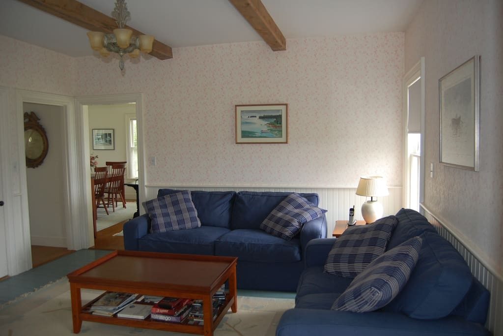 Family room, two comfortable couches and coffee table. View to living and dining room beyond.