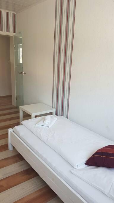 Einzelzimmer mit Bett, Schrank und Kommode