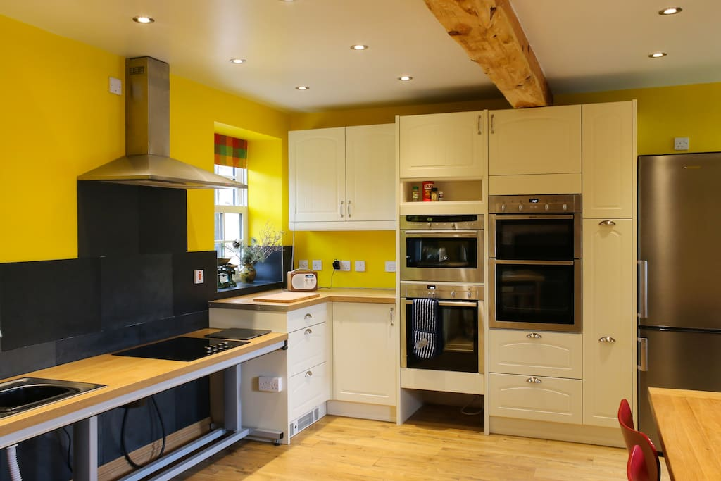 Kitchen showing multi-height ovens and rise and fall sink/hob/worktop in lowered position