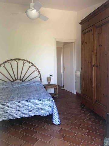Camera matrimoniale con porta che da sul giardino dietro. Lo spazio esterno è attrezzato con tavolo e sedie. Vista su Porto Azzurro.