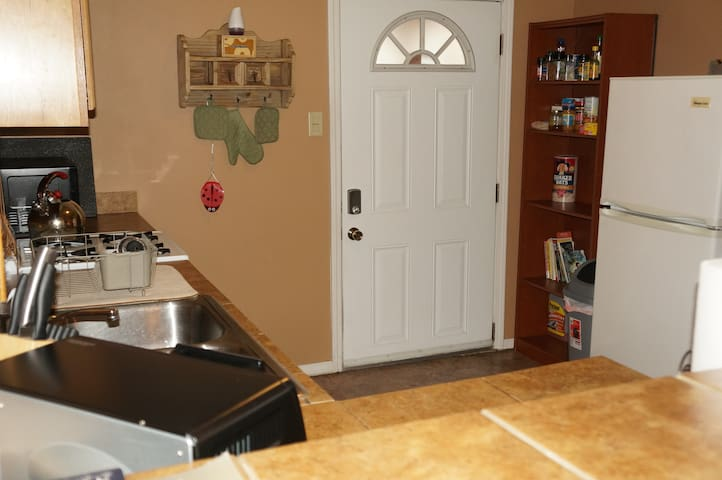 Kitchen with fridge, filtered water, gas stove, pots/pans, toaster oven, coffee station, microwave, glassware etc.