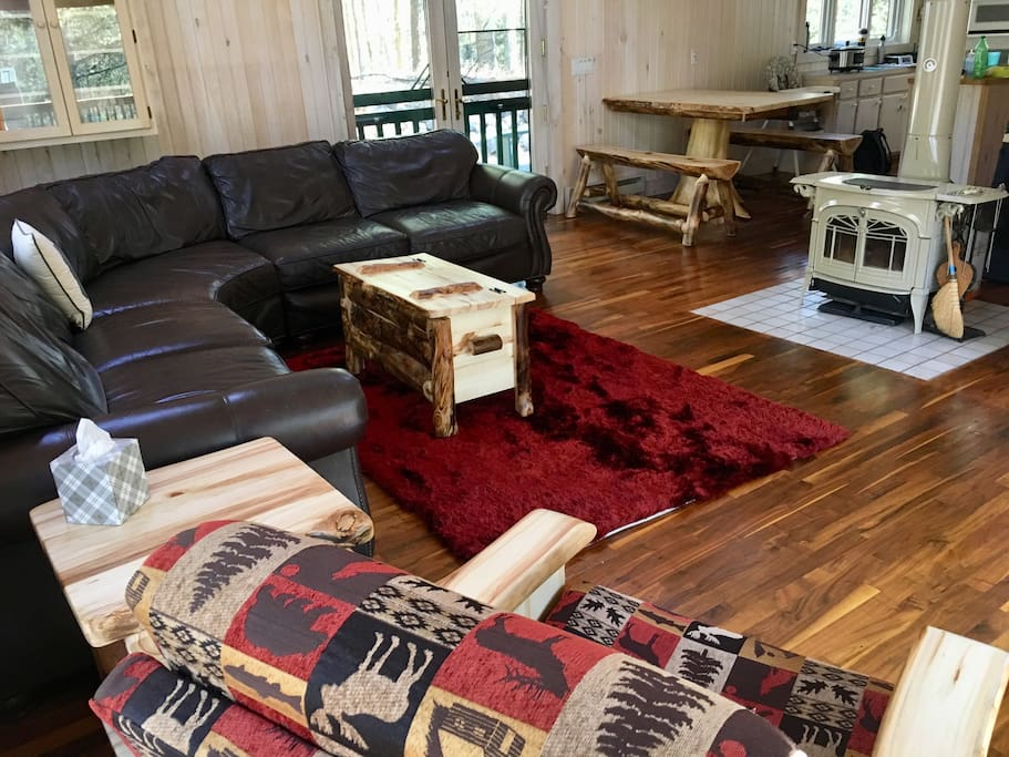 The main room, with plenty of seating for groups, a wall mounted tv, and a wood burning fireplace.