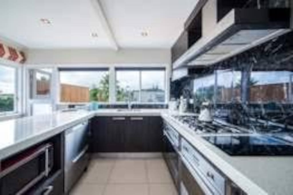 Large entertainer's kitchen leading onto sunny deck
