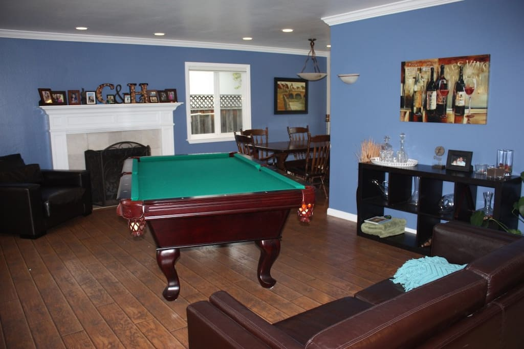 Living room, pool table, fire place, dining room.