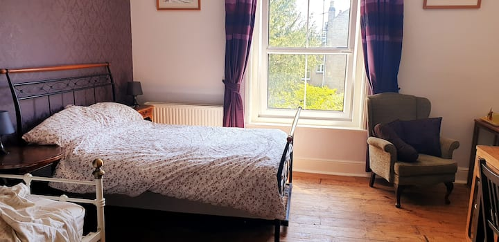 Large room with a double and single bed .