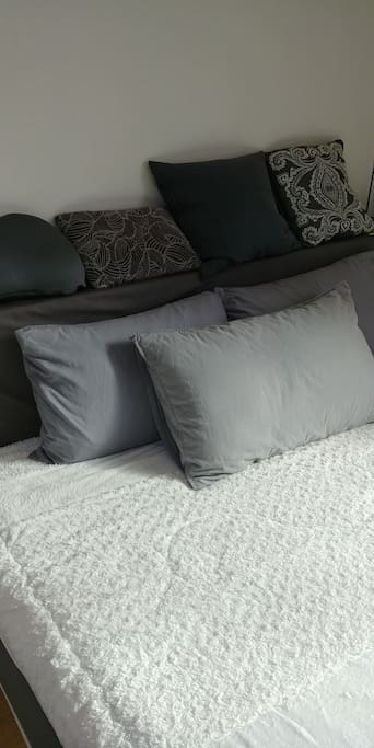 A king size bed with many pillows