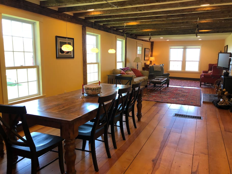 The renovated, open living area includes dining room with a custom table for 8-12, living room, and sitting area