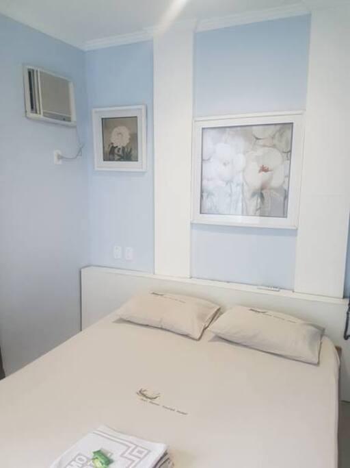 Quarto com ar condicionado, TV e roupa de cama