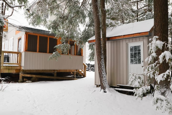 """A snowy look at the """"Anchor Bunkie""""/Bedroom #4 surrounded by beautiful trees which keep the space nice and shaded and cool in the summertime. It also houses a set of bunkbeds and an additional window."""