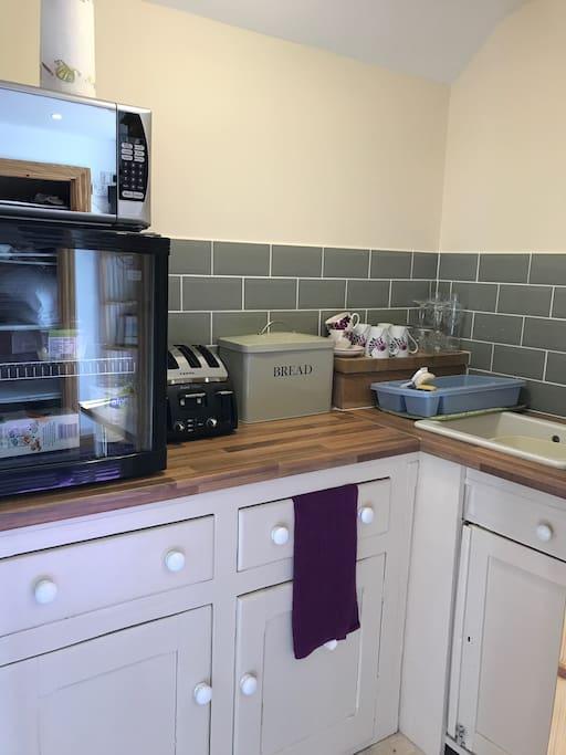 Kichennette.  Kettle, toaster, microwave, fridge, sink, crockery, cutlery and glasses.