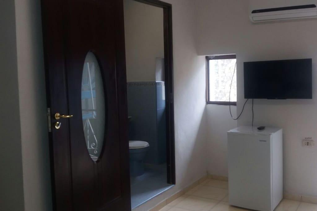 Baño. Bathroom. TV y nevera. TV and mini freezer