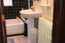 First floor full bathroom with tile floor & walls. Nice Pedestal sink & large mirror.