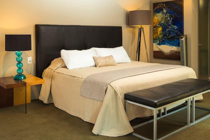 Amplia y acogedora habitacion king size  con cuarto de baño independiente, área de trabajo, cocineta y terraza.
