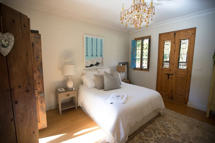 House bedroom with doors to verandah with couch and hammock.