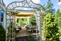 "The garden trellis is our entry point to the covered patio and garden pergola that overlooks ""la fontaine de quatre grenouilles cracheuses."""