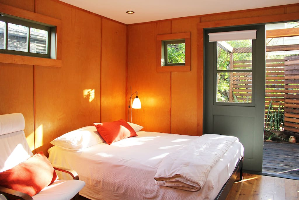 queen size bed with view of private garden deck