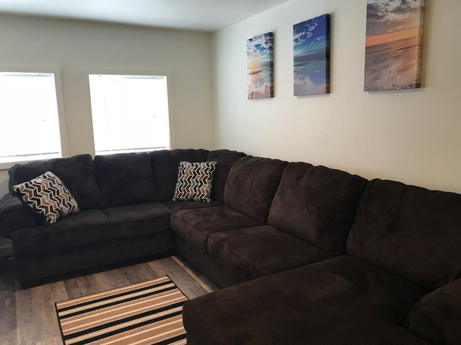 Large cozy sectional couch in main living space with wide-screen Roku TV featuring Roku programming