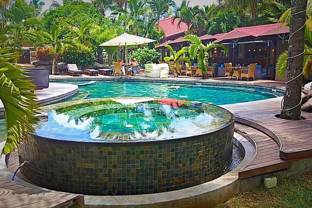 Swimming pool with seating area around within the pool.
