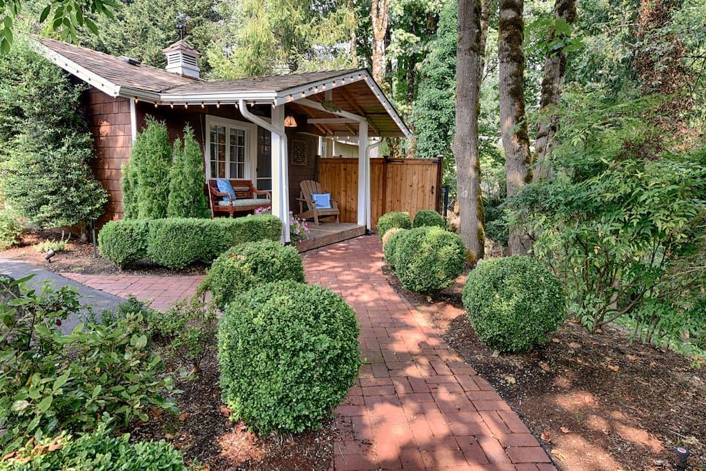 Brick pathway leads to cottage, creating a beautiful courtyard and woods effect.