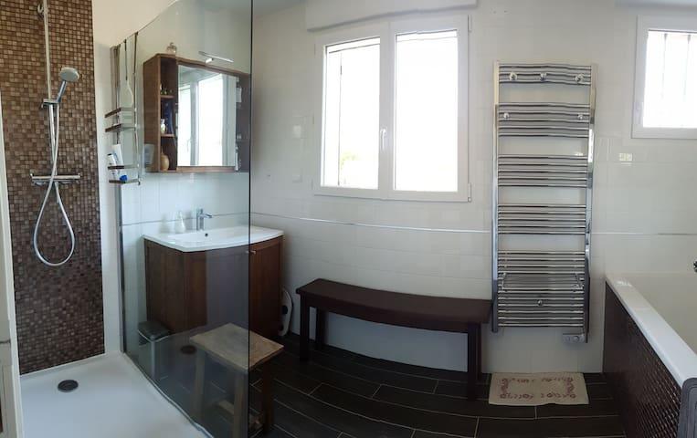 Salle de bain avec grande douche et grande baignoire.