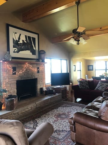 Living room with vaulted ceiling, leather couch, Direct TV, hand knotted rug, and plenty of seating for you to enjoy the hill country view  Open concept with kitchen and dining is convenient and great for entertaining