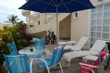 terraza con 2 Canasteros, mesa con 4 sillas y sombrilla de sol 2 bicis al fondo