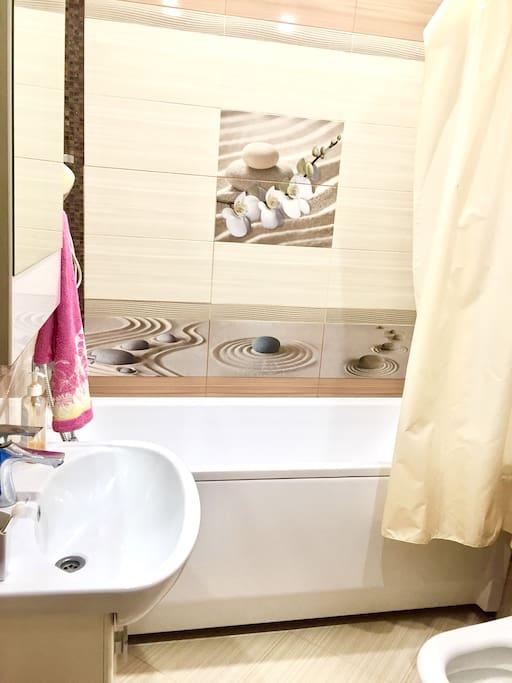 Ванная комната, полотенца, мыльные принадлежности, фен, стиральная машина.
