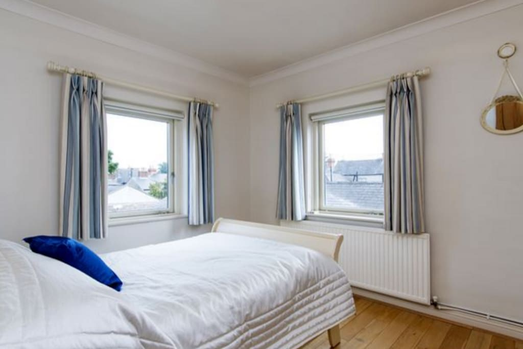 The bedroom is a beautiful dual aspect room with double bed and plenty of storage