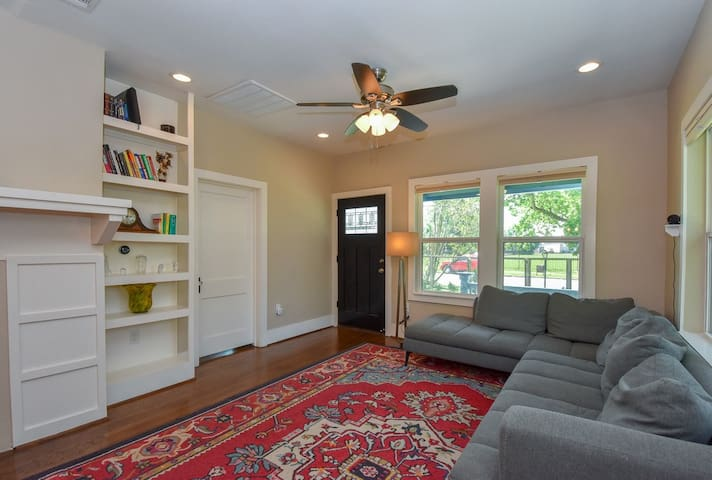 Door to the right of the built-in bookshelf and fireplace leads to bedroom 1.