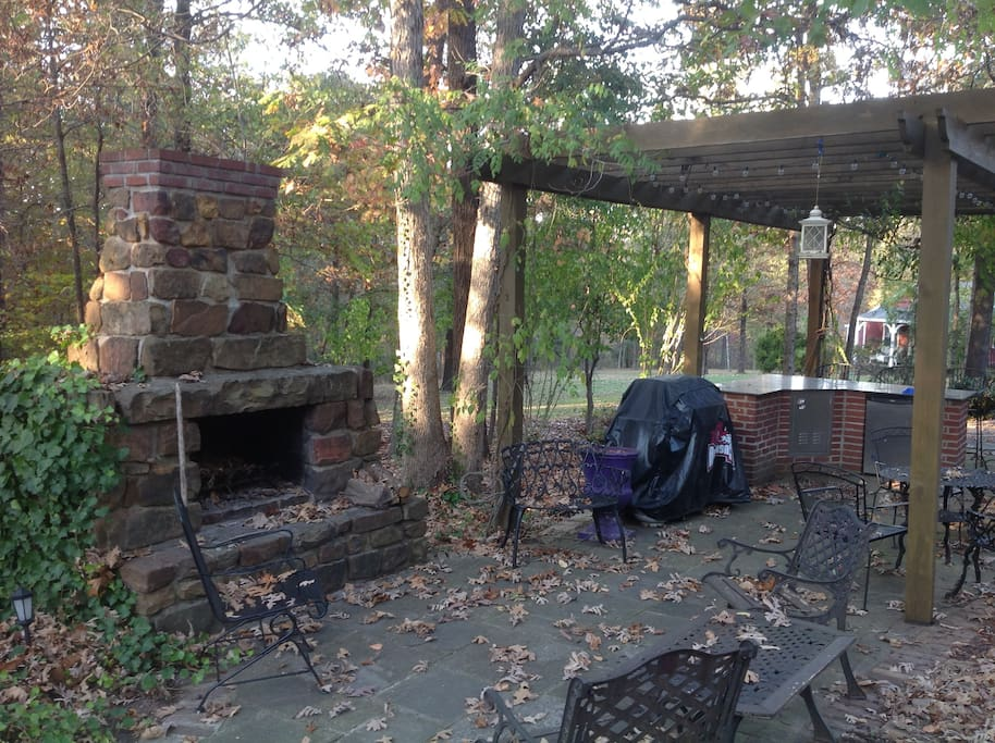 lighted outdoor kitchen area with grill, fireplace, and fridge