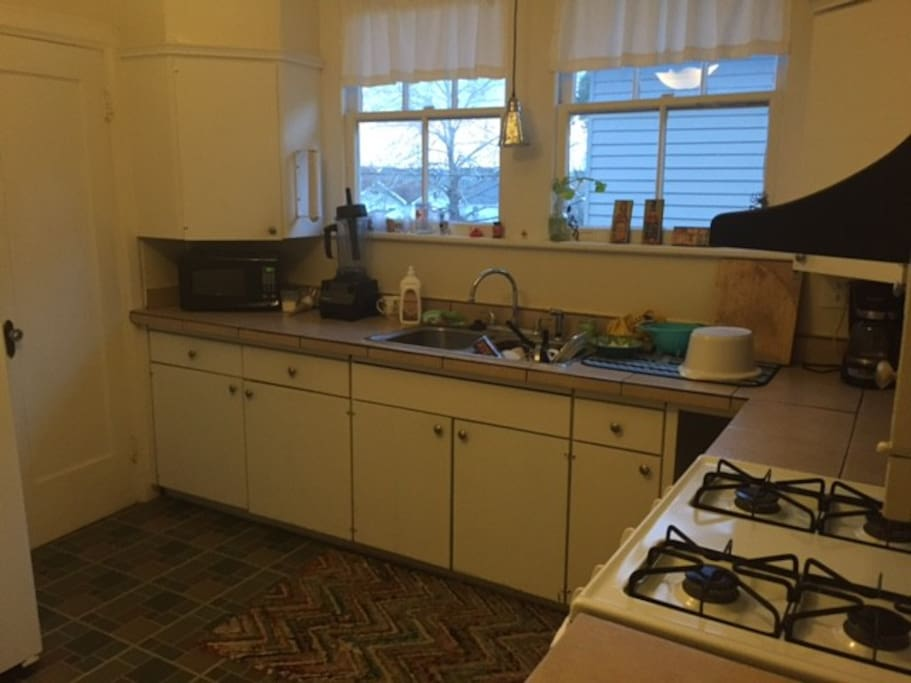 Kitchen with fridge, microwave, oven, coffee pot, etc.