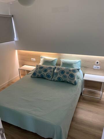 Dormitorio con cama de matrimonio de 150 cm, 2 mesitas de noche, espejo con repisa y armario empotrado con cajones, estantes y perchas...