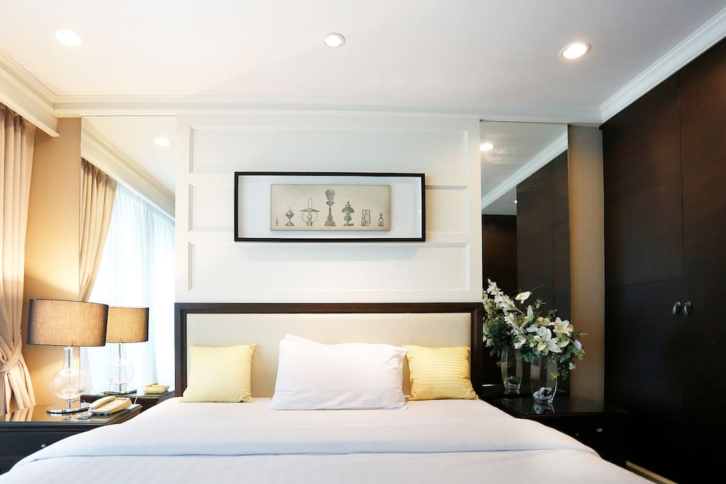 Spacious master bedroom with wall mirrors on both sides of the bed