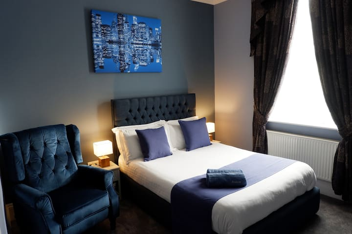 Wonderful large en-suite room, with everything you need for a short or long stay in the centre of Exeter, smart TV, work desk, built under fridge freezer, easy recline chairs, en-suite with rain forest shower, towels, laundry, iron, hair dryer etc