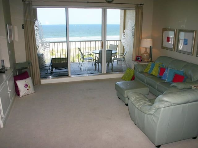 The spacious, oceanfront living room features a cozy leather couch and love seat, large flat screen TV and DVD.