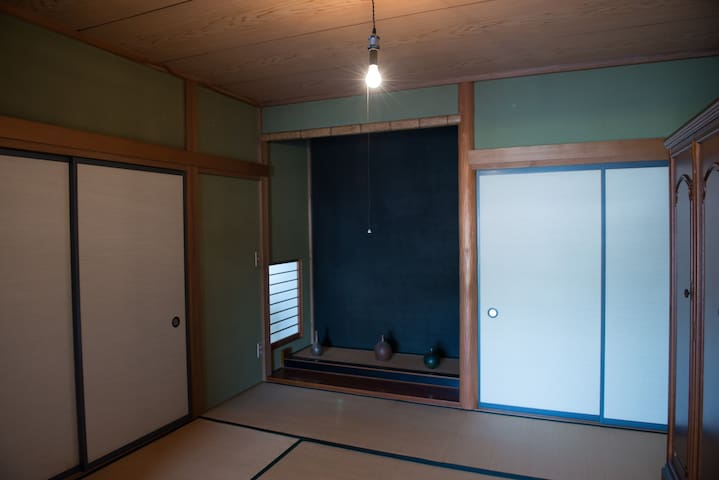 Tatami room with traditional Tokonoma. You are going to sleep spreading Futon in this room. (Caution: No key lock, only sliding door)