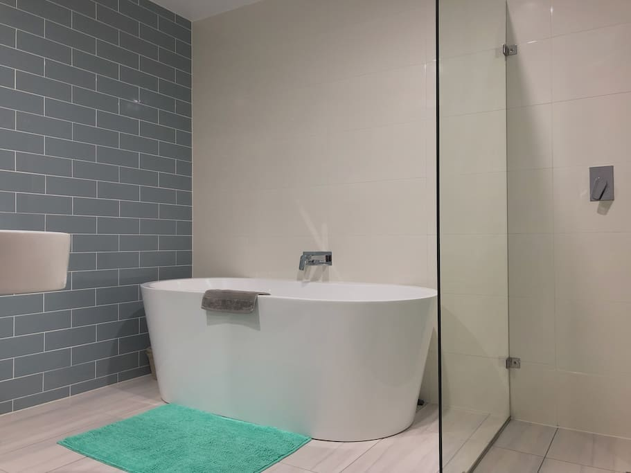 Ensuite bathroom with bathtub and shower