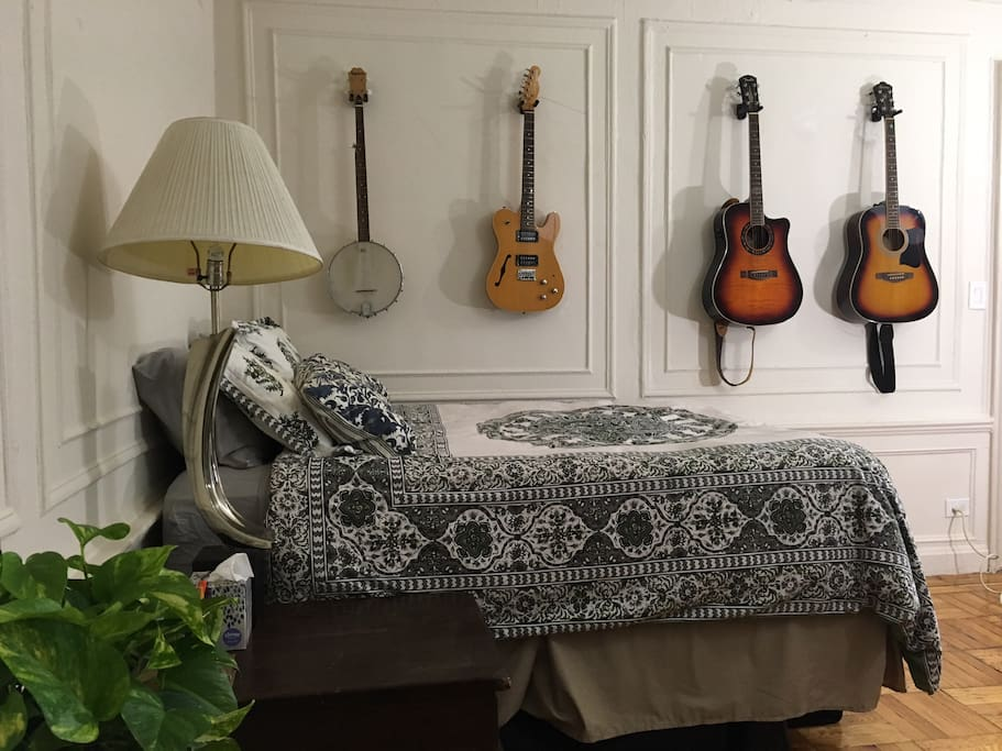 Double bed, assorted guitars.