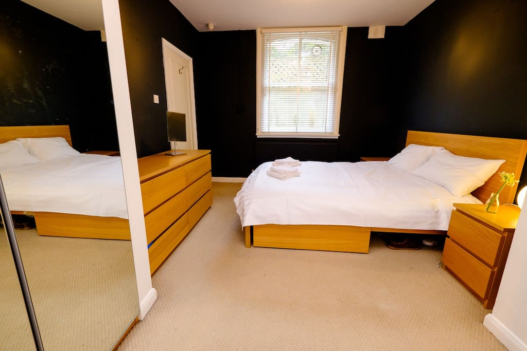 Double bed in spacious bedroom with en suite bathroom and plenty of storage space