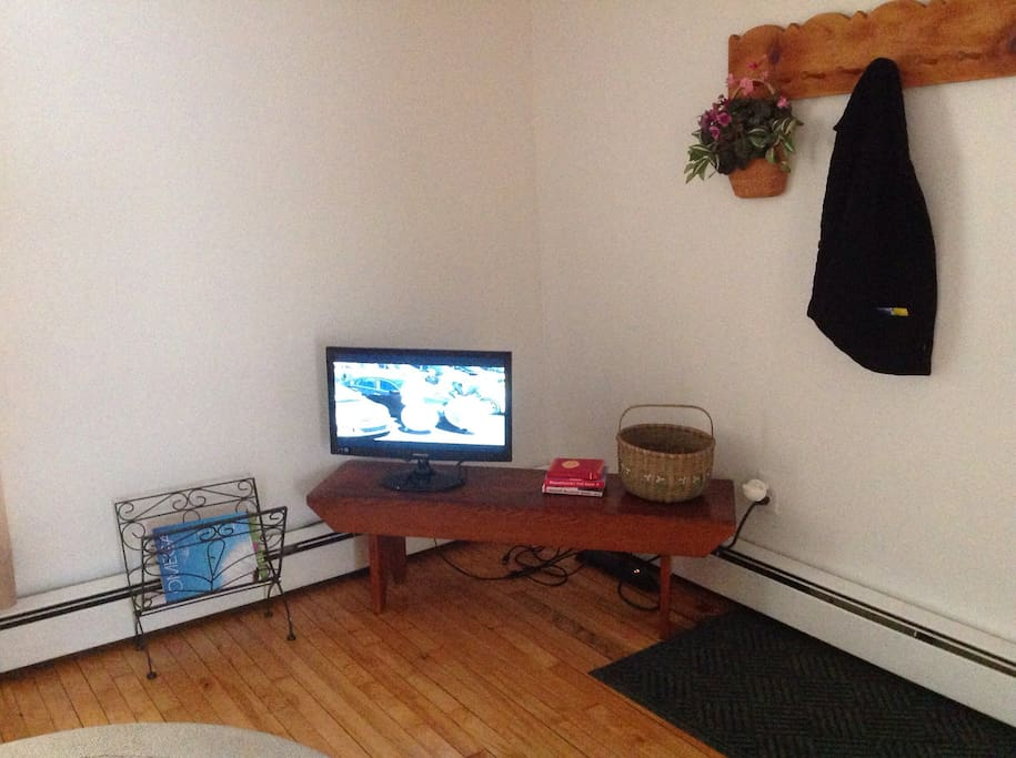 Flat screen tv and coat rack in living room area