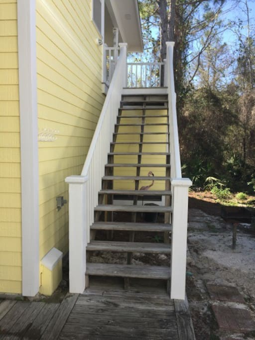Rear stairway leads up to apartment entry door.