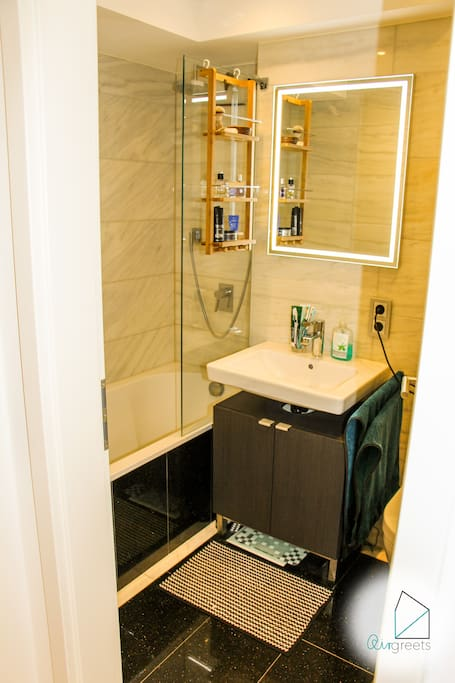 The bathroom has a tub with an integrated shower.